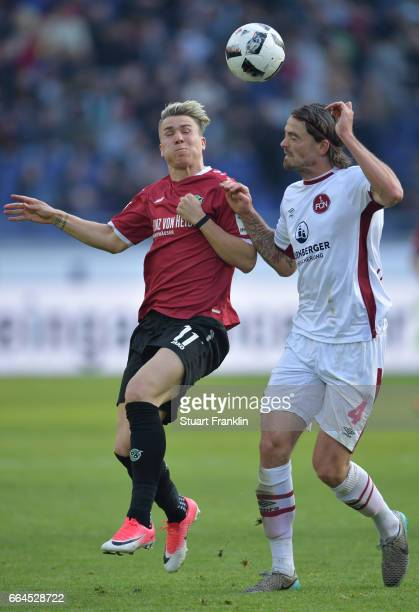 Felix Klaus of Hannover is challenged by Dave Bulthuis of Nuernberg during the Second Bundesliga match between Hannover 96 and 1 FC Nuernberg at...