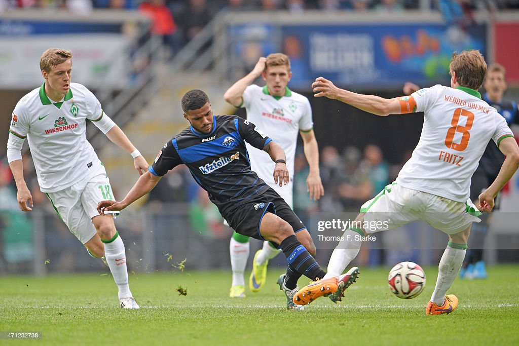 Felix Kroos and Clemens Fritz of Bremen tackle Elias Kachunga of Paderborn during the Bundesliga match between SC Paderborn and SV Werder Bremen at...