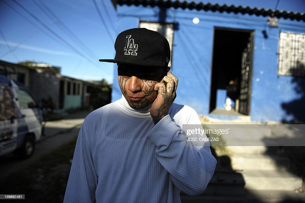 Felix, of the 18th street gang, talks on the phone outside a bakery operated by gang members as a part of a rehabilitation program in San Bartolo neigbourhood, in Ilopango, a suburb of San Salvador on January 21, 2012. Gang leaders started the second phase of the gang truce to reduce crime in El Salvador. AFP PHOTO/ Jose CABEZAS