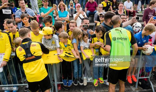 Felix Passlack and Oemer Toprak of Borussia Dortmund are giving autographs to the fans after a training session as part of the training camp on July...
