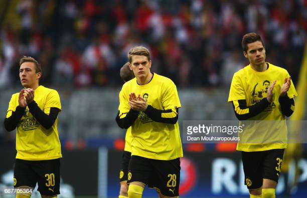 Felix Passlack Matthias Ginter and Julian Weigl of Borussia Dortmund wear shirts for Marc Bartra who was injured in the team coach attack prior to...