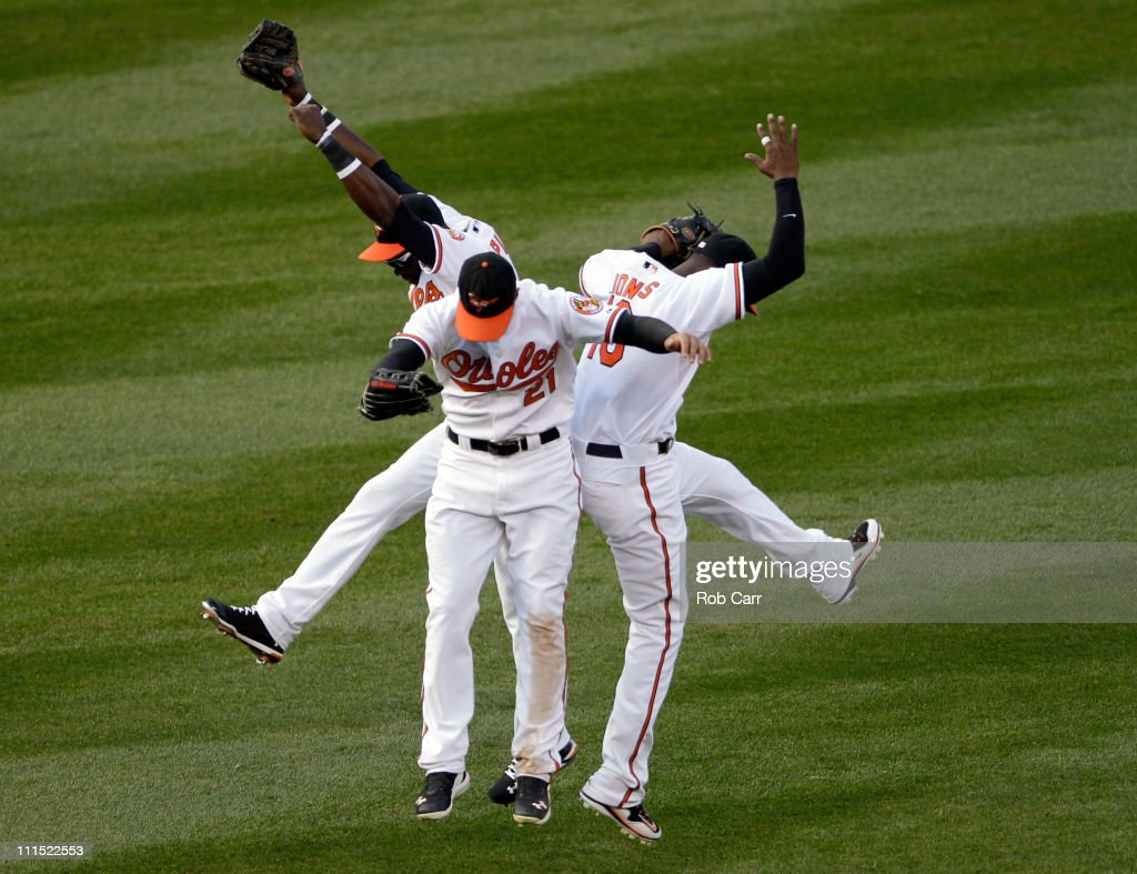 Felix Pie #18 of the Baltimore Orioles (L) and teammates Nick Markakis #21 (C) and Adam Jones #10 celebrate in the outfield after the Orioles defeated the Detroit Tigers 5-1 during opening day at Oriole Park at Camden Yards on April 4, 2011 in Baltimore, Maryland.