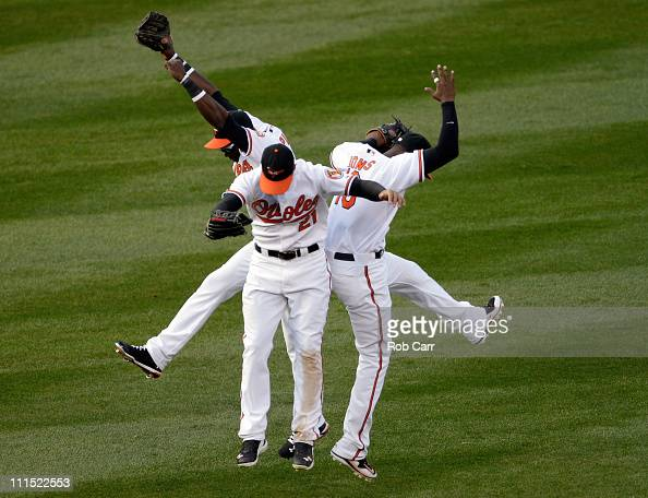 Felix Pie of the Baltimore Orioles and teammates Nick Markakis and Adam Jones celebrate in the outfield after the Orioles defeated the Detroit Tigers...
