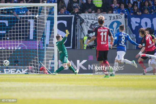 Felix Platte of Darmstadt scores his team's first goal past Alexander Schwolow of Freiburg during the Bundesliga match between SV Darmstadt 98 and SC...