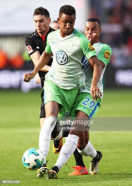 Felix Uduokhai of VfL Wolfsburg is challenged by Marcel Tisserand of VfL Wolfsburg and Lucas Alario of Bayer Leverkusen during the Bundesliga match...