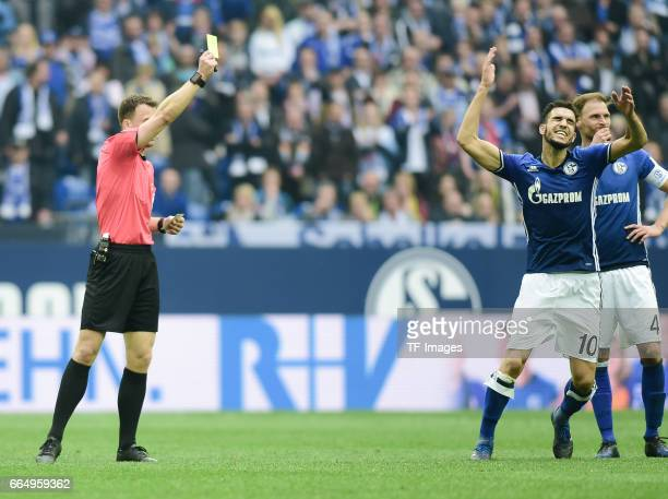Felix Zwayer gievs Nabil Bentaleb of Schalke the yellow card during the Bundesliga match between FC Schalke 04 and Borussia Dortmund at VeltinsArena...