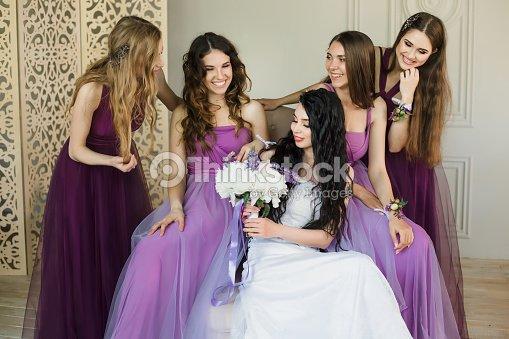 263c53701 La tala entusiasmado con la boda. Atractivo joven novia con un ramo de novia  y sonriendo mientras hablaba con sus encantadoras damas de honor en vestidos  de ...