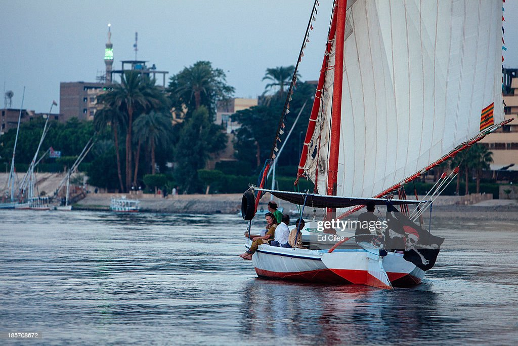 A felluca a traditional Egyptian sail boat sails with a small group of tourists aboard along the Nile River on October 23 2013 in Luxor Egypt Luxor...