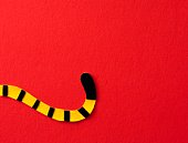 Felt tiger's tail, red background, copy space
