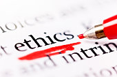 """A red felt-tipped pen underscores the word """"ethics"""" on a printed page."""