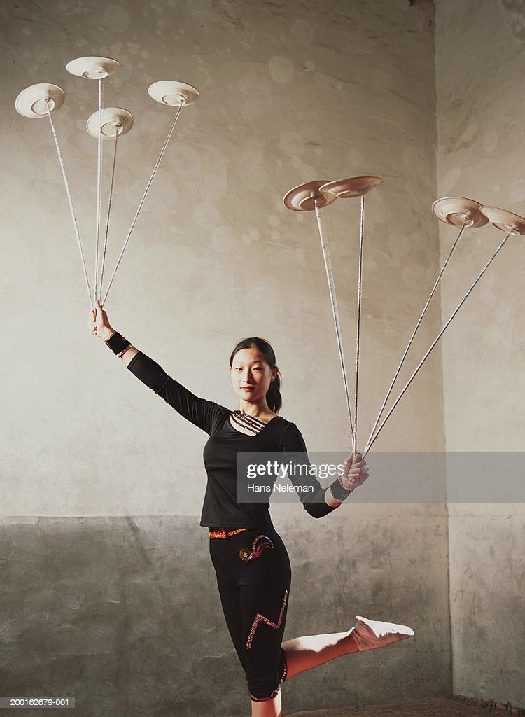 Female acrobat balancing plates on sticks, portrait : Stock Photo