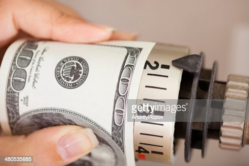 Female Adjusting Thermostat With Banknote : Stockfoto