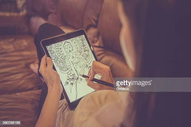 Female AdultDrawing Mandala on Electronic Tablet