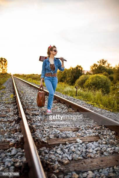 Female adventurous walking with acoustic guitar and suitcase on the railroad