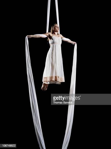Female aerialist performing on suspended silk