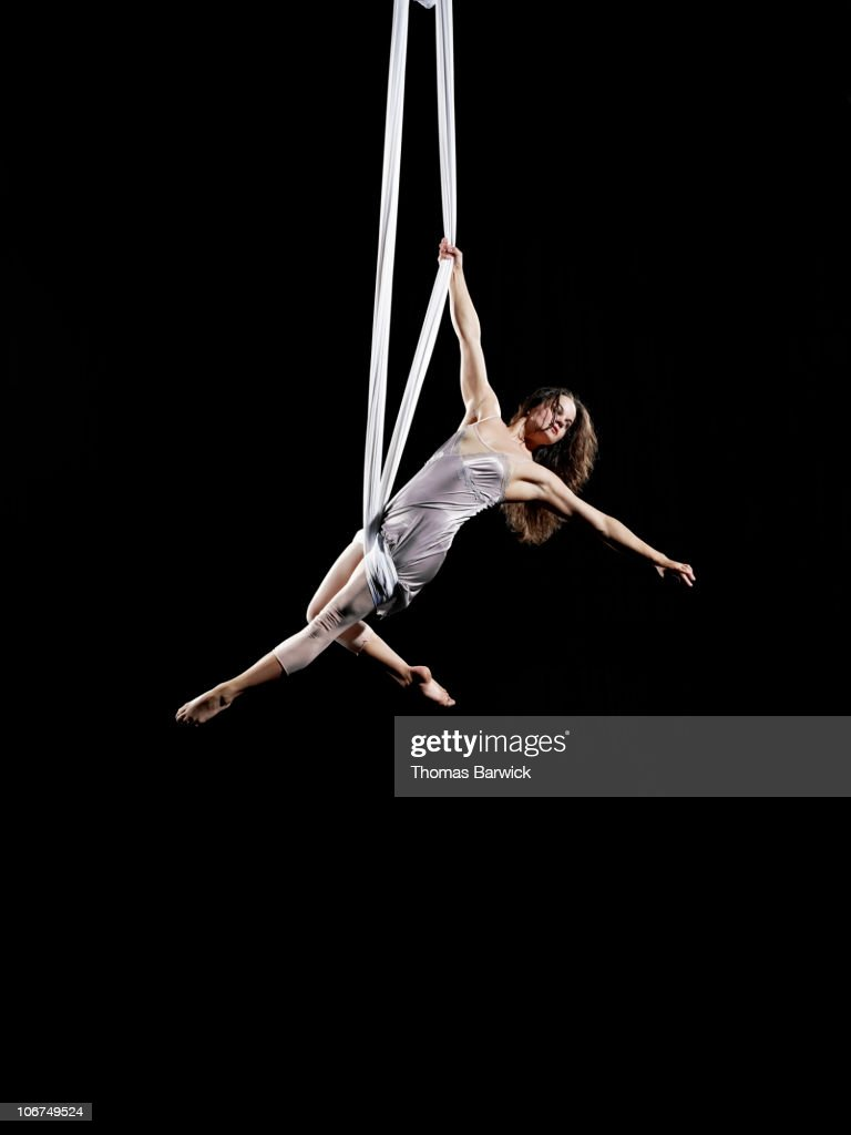 Female aerialist performing on suspended silk : Stock Photo