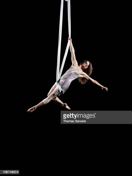 Female aerialist performing on suspended silk
