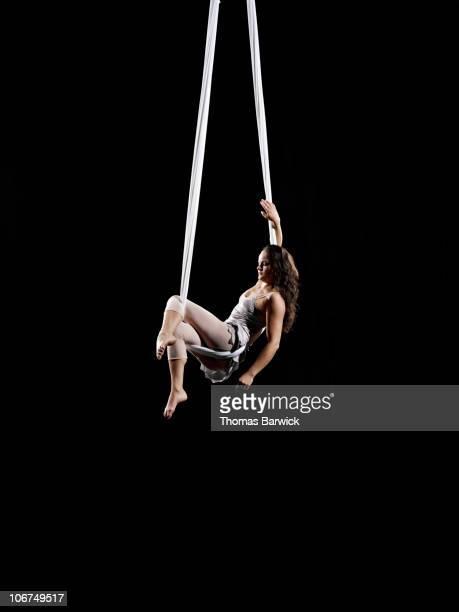 Female aerialist seated on suspended silk