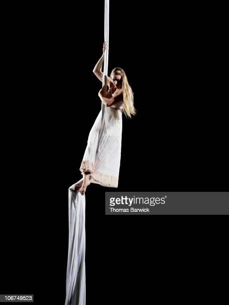 Female aerialist sliding down suspended silk