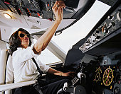 Female aeroplane pilot, operating controls, low angle view