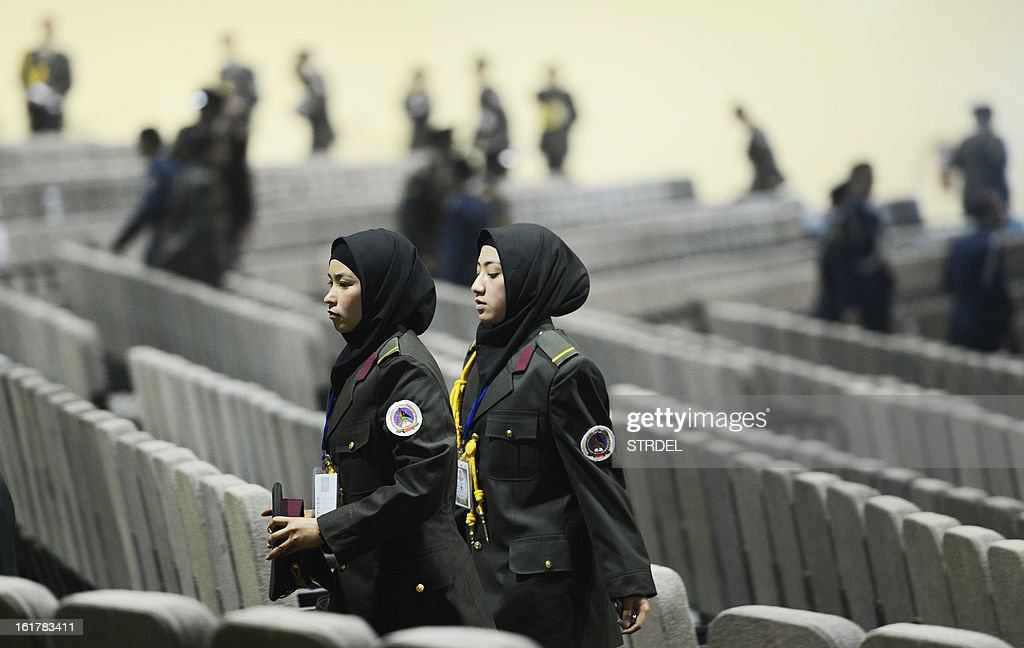 Female Afghan National Army officers leave the hall during a conference attended by Afghan President Hamir Karzai at the National Miltary Academy in Kabul on February 16, 2013. Afghanistan has committed to taking full responsibility for its own security after US forces leave, and the White House said Afghan security forces now count 352,000 troops, thanks to a broad NATO training effort. AFP PHOTO/STR