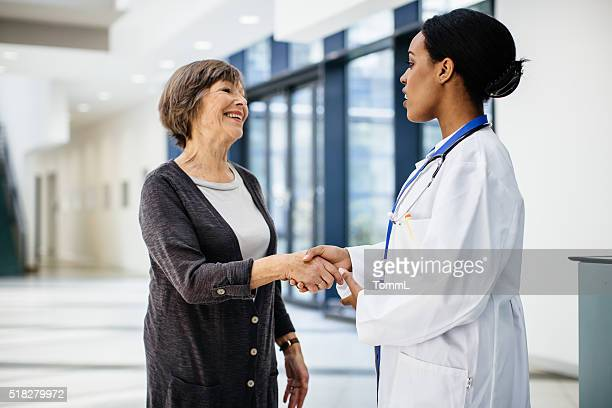 Female african doctor welcomes senior patient