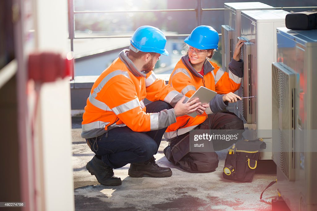 female air conditioning technician with her supervisor : Stock Photo