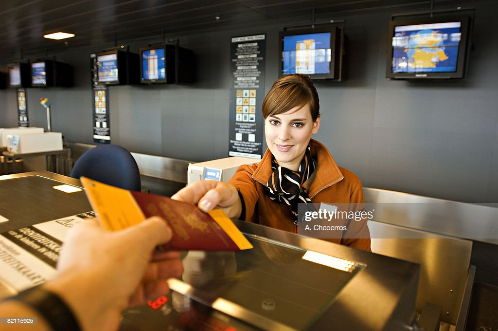 Female airline check-in attendant giving a passport and boarding pass to a passenger