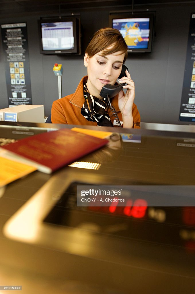 Female airline check-in attendant talking on the telephone
