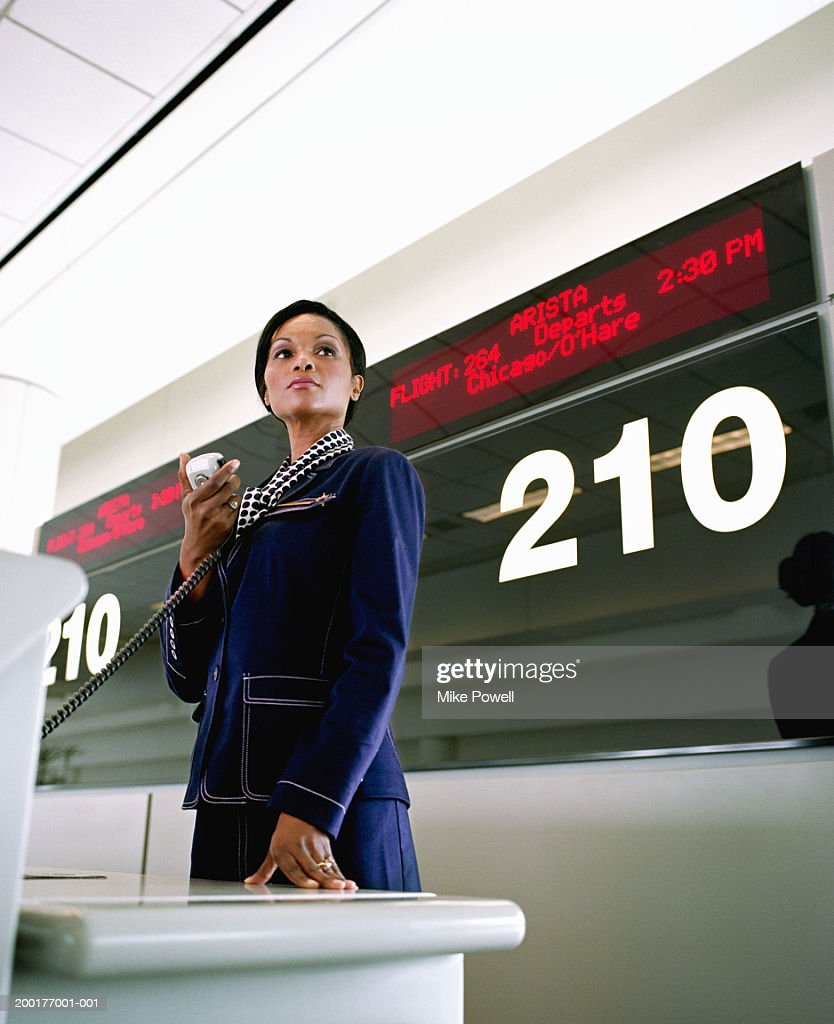 Female airline worker holding public address system microphone