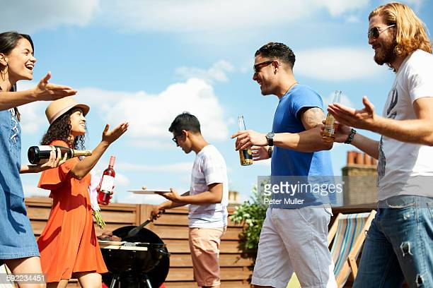 Female and male friends greeting at rooftop barbecue