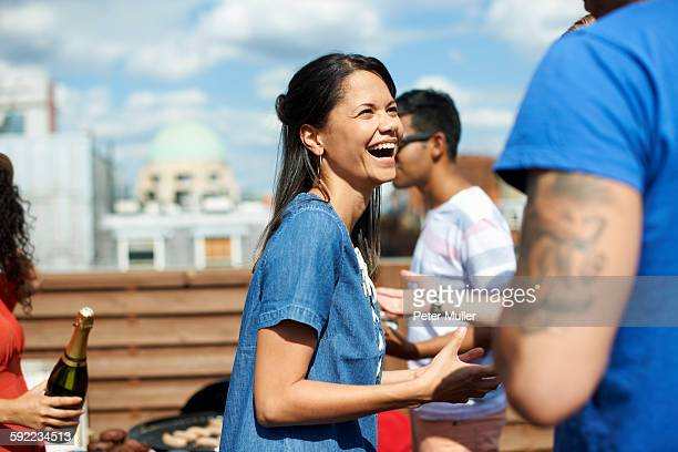 Female and male friends laughing and chatting at rooftop barbecue