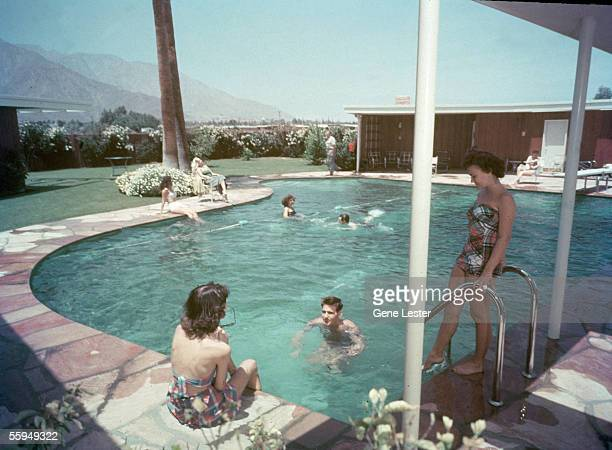 Female and male guests relax near and swim in the pianoshaped swimming pool at Twin Palms the estate belonging to American singer and actor Frank...