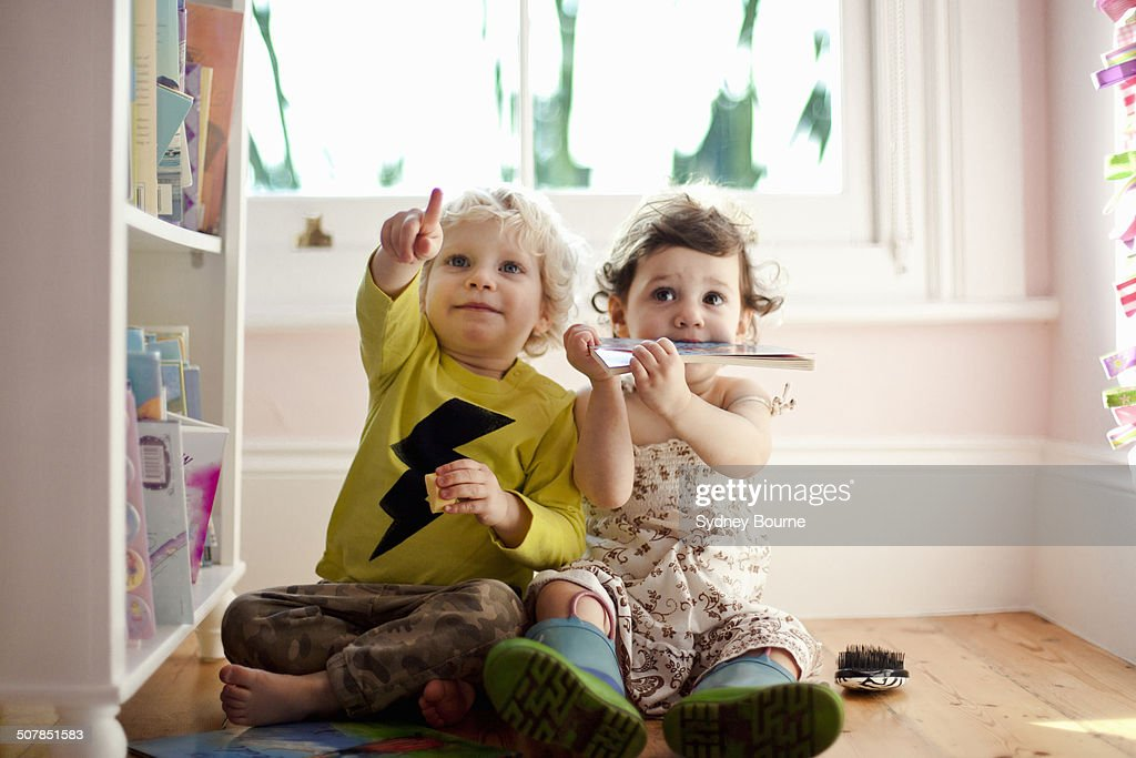 Female and male toddler friends pointing and looking up