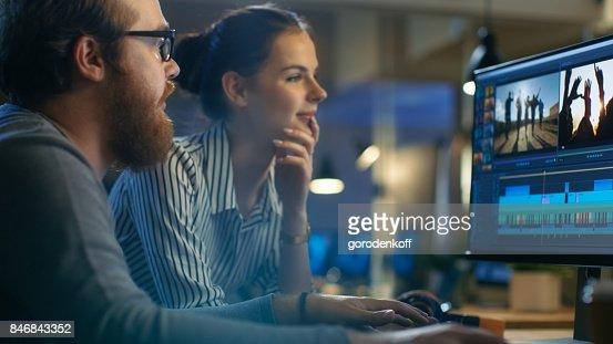 Weibliche und männliche Video-Editoren Arbeit mit Filmmaterial und Sound auf ihrem PC mit zwei Displays. Sie sind schöne und kreative Menschen und deren Büro ist modernen Loft. : Stock-Foto