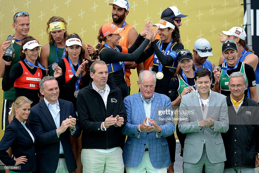 Female and male winners celebrate with officials on the podium during the FIVB Grand Slam final match day at The Hague Beach Stadium on June 16, 2013 in The Hague, Netherlands.