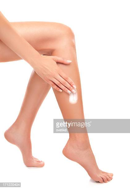 Female applying cream on legs