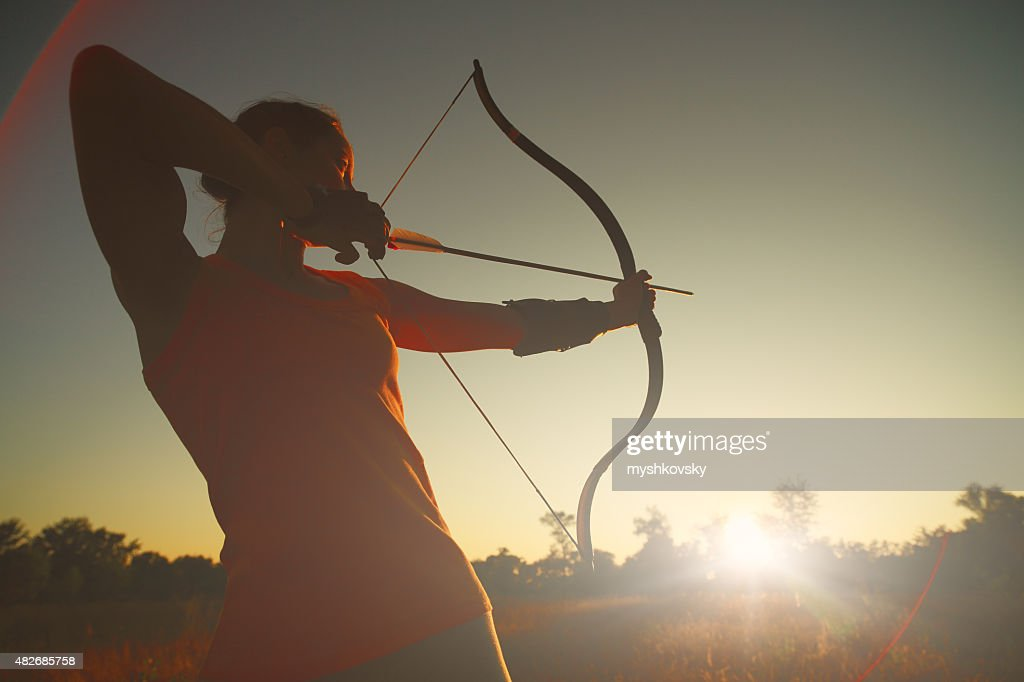 Female archer in the field at sunset : Stock Photo