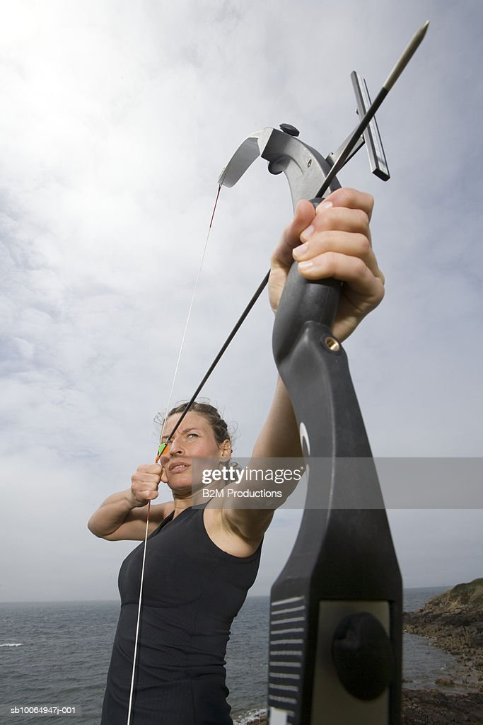 Female archer standing at sea shore aiming arrow : Stock Photo