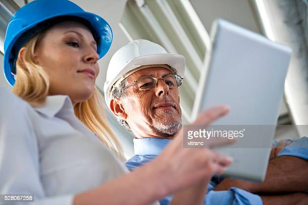 Femme architecte et Construction Travailleur discuter sur place