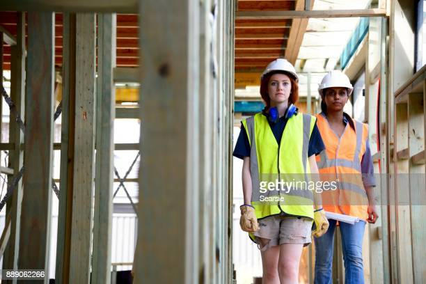 SYD112017 Female Architect and construction worker walking through the house frame