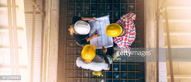 Female architect and two consruction workers on a construction site