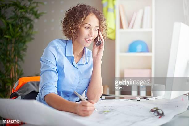 female architect checking blueprints