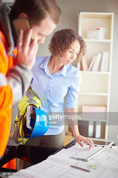 female architect checking blueprints with building contractor