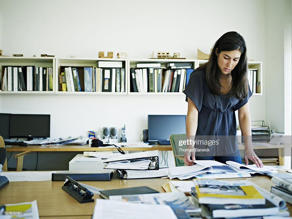 Female architect examining documents at desk : Stock Photo