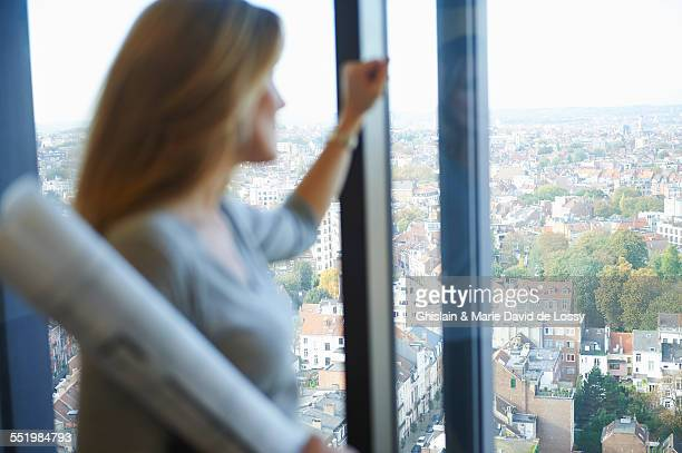 Female architect gazing from office window at Brussels cityscape, Belgium