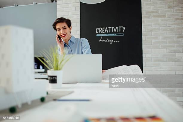 Donna architetto al telefono nel suo ufficio.