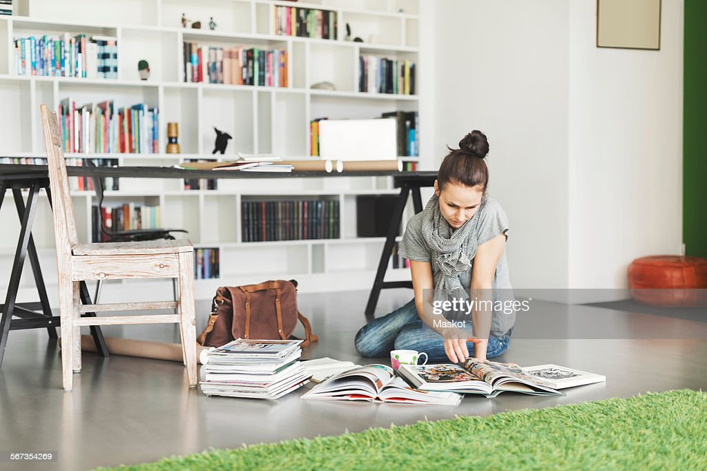 Female architect reading magazine on floor at home office