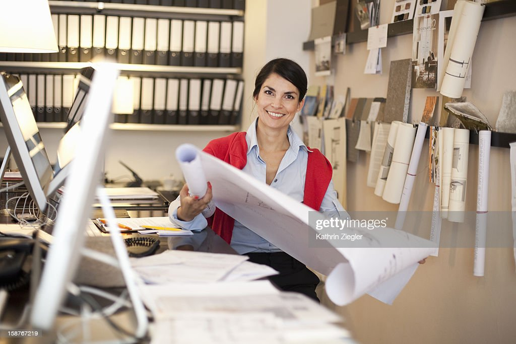 female architect unrolling plans at desk : Stock Photo