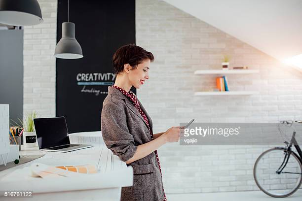 Femme architecte à l'aide de téléphone intelligent dans son bureau.
